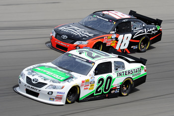 LAS VEGAS, NV - MARCH 05:  Denny Hamlin, driver of the #20 Interstate Batteries Toyota, and Kyle Busch, driver of the #18 Z-Line Designs Toyota, race side by side during the NASCAR Nationwide Series Sam's Town 300 at Las Vegas Motor Speedway on March 5, 2