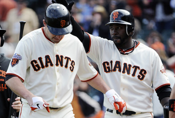 SAN FRANCISCO, CA - JUNE 11: Pat Burrell #5 (L) of the San Francisco Giants is slapped on the helmet by teammate Bill Hall #29 (R) after Burrell hit a two run home run in the bottom of the ninth inning against the Cincinnati Reds during a MLB baseball gam
