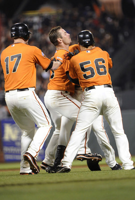 SAN FRANCISCO, CA - JUNE 10: Nate Schierholtz #12 of the San Francisco Giants after getting the game winning his is smothered by teammates Andres Torres #56, Aaron Rowand #33 and Aubrey Huff #17 during a MLB baseball game against the Cincinnati Reds June