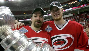RALEIGH, NC - JUNE 19:  Justin Williams #11 and Eric Staal #12 of the Carolina Hurricanes celebrate with the Stanley Cup after defeating the Edmonton Oilers in game seven of the 2006 NHL Stanley Cup Finals on June 19, 2006 at the RBC Center in Raleigh, No