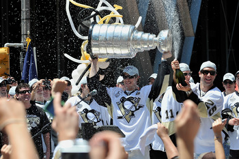 PITTSBURGH - JUNE 15:  Sidney Crosby #87 of the Pittsburgh Penguins holds the Stanley Cup as Maxime Talbot #25 of the Penguins sprays the crowd during Stanley Cup Champion Victory Parade on June 15, 2009 in Pittsburgh, Pennsylvania.  (Photo by Jamie Sabau