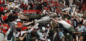 EAST RUTHERFORD, NJ - JUNE 9:  Scott Stevens of the New Jersey Devils carries the Stanley Cup holds up the Stanley Cup after beating the Mighty Ducks of Anaheim in game seven of the 2003 Stanley Cup Finals at Continental Airlines Arena on June 9, 2003 in