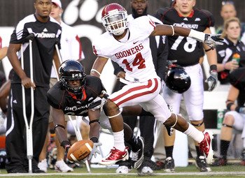 CINCINNATI - SEPTEMBER 25:  Armon Binns #80 of the Cincinnati Bearcats reaches up for a pass while defended by Aaron Colvin #14 of the Oklahoma Sooners during the game at Paul Brown Stadium on September 25, 2010 in Cincinnati, Ohio. The pass fell incomple