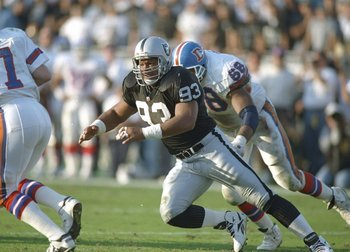 9 Jan 1994:  Defensive lineman Greg Townsend of the Los Angeles Raiders (center) goes after Denver Broncos quarterback John Elway (left) during a playoff game at the Los Angeles Memorial Coliseum in Los Angeles, California.  The Raiders won the game, 42-2