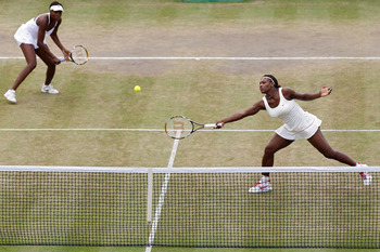 LONDON, ENGLAND - JUNE 30:  Serena Williams (R) and Venus Williams of USA in action during their Quarter Final doubles match against Elena Vesnina and Vera Zvonareva of Russia on Day Nine of the Wimbledon Lawn Tennis Championships at the All England Lawn