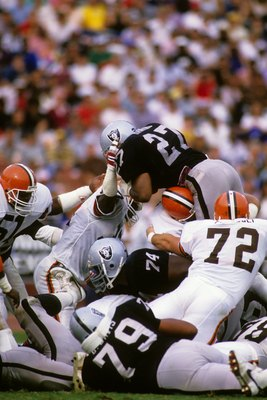 LOS ANGELES - NOVEMBER 16: Running back Frank Hawkins #27 of the Los Angeles Raiders jumps over the line of scrimmage including teammate Shelby Jordan #74 and Dave Puzzuoli #72 of the Cleveland Browns during the game at the Los Angeles Memorial Coliseum o