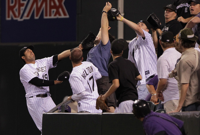 DENVER, CO - JUNE 10:  Ryan Spilborghs #19 of the Colorado Rockies fails to catch a foul ball that is caught by a fan in the rightfield stands in the ninth inning at Coors Field on June 10, 2011 in Denver, Colorado.  (Photo by Doug Pensinger/Getty Images)