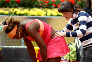MADRID, SPAIN - MAY 10:  Serena Williams of the USA receives treatment for an injury from the tour doctor against Vera Dushevina of Russia in their second round match during the Mutua Madrilena Madrid Open tennis tournament at the Caja Magica on May 10, 2