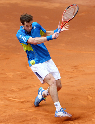MADRID, SPAIN - MAY 12:  Andy Murray of Great Britain slides on the clay to play a backhand against Juan Ignacio Chela of Argentina in their second round match during the Mutua Madrilena Madrid Open tennis tournament at the Caja Magica on May 12, 2010 in