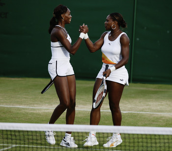 LONDON - JUNE 30:  Venus and Serena Williams of the USA celebrate winning their Ladies Doubles match on the seventh day of the Wimbledon Lawn Tennis Championships held on June 30, 2003 at the All England Lawn Tennis and Croquet Club, in London. (Photo by