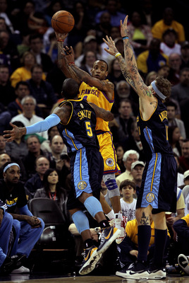 OAKLAND, CA - JANUARY 20:  Monta Ellis #8 of the Golden State Warriors passes over J.R. Smith #5 and Chris Anderson #11 of the Denver Nuggets at Oracle Arena on January 20, 2010 in Oakland, California.  NOTE TO USER: User expressly acknowledges and agrees