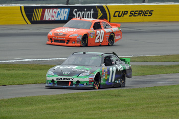 LONG POND, PA - JUNE 12:  Denny Hamlin, driver of the #11 FedEx Ground Toyota, drives down pit road with a flat rear left tire as Joey Logano, driver of the #20 The Home Depot Toyota, passes during the NASCAR Sprint Cup Series 5-Hour Energy 500 at Pocono