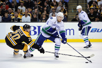 BOSTON, MA - JUNE 13:  Daniel Paille #20 of the Boston Bruins fights for the puck against Christian Ehrhoff #5 of the Vancouver Canucks during Game Six of the 2011 NHL Stanley Cup Final at TD Garden on June 13, 2011 in Boston, Massachusetts.  (Photo by Ha