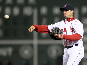 BOSTON, MA - APRIL 30:  Marco Scutaro #10 of the Boston Red Sox sends the ball to first for the out against the Seattle Mariners on April 30, 2011 at Fenway Park in Boston, Massachusetts.  (Photo by Elsa/Getty Images)