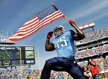NASHVILLE, TN - NOVEMBER 21:  Ahmard Hall #45 of the Tennessee Titans, an armed services veteran, brings out the American flag before a game against the Washington Redskins at LP Field on November 21, 2010 in Nashville, Tennessee.  (Photo by Grant Halvers