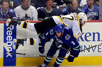 VANCOUVER, BC - JUNE 10:  Milan Lucic #17 of the Boston Bruins gets checked by Kevin Bieksa #3 of the Vancouver Canucks during Game Five of the 2011 NHL Stanley Cup Final at Rogers Arena on June 10, 2011 in Vancouver, British Columbia, Canada.  (Photo by