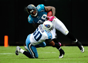 JACKSONVILLE, FL - OCTOBER 04:  Marcedes Lewis #89 of the Jacksonville Jaguars is tackled by David Thornton #50 of the Tennessee Titans during the game at Jacksonville Municipal Stadium on October 4, 2009 in Jacksonville, Florida.  (Photo by Sam Greenwood