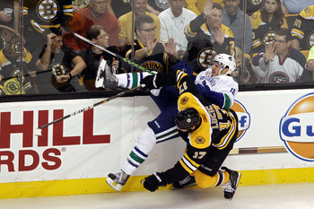 BOSTON, MA - JUNE 13:  Chris Tanev #18 of the Vancouver Canucks collides with Milan Lucic #17 of the Boston Bruins during Game Six of the 2011 NHL Stanley Cup Final at TD Garden on June 13, 2011 in Boston, Massachusetts.  (Photo by Bruce Bennett/Getty Ima