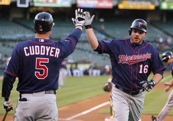OAKLAND, CA - MAY 18:  Jason Kubel #16 is congratulated by Michael Cuddyer #5 of the Minnesota Twins after he scored in the first inning against the Oakland Athletics at Oakland-Alameda County Coliseum on May 18, 2011 in Oakland, California.  (Photo by Ez