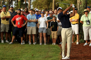 PONTE VEDRA BEACH, FL - MAY 12:  Tiger Woods hits from the rough on the first hole in front of a gallery of fans during the first round of THE PLAYERS Championship held at THE PLAYERS Stadium course at TPC Sawgrass on May 12, 2011 in Ponte Vedra Beach, Fl