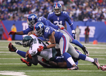 EAST RUTHERFORD, NJ - DECEMBER 19:  Justin Tuck #91, Michael Boley #59, and Antrel Rolle #26 of the New York Giants tackle Michael Vick #7 of the Philadelphia Eagles during their game on December 19, 2010 at The New Meadowlands Stadium in East Rutherford,