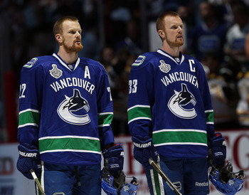 VANCOUVER, BC - JUNE 10:  Daniel Sedin #22 and Henrik Sedin #33 of the Vancouver Canucks look on prior to Game Five of the 2011 NHL Stanley Cup Final at Rogers Arena on June 10, 2011 in Vancouver, British Columbia, Canada.  (Photo by Bruce Bennett/Getty I