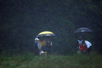 FARMINGDALE, NY - JUNE 20:  Camilo Villegas of Colombia and Stewart Cink stand with their caddies under umbrellas in the rain during the third round of the 109th U.S. Open on the Black Course at Bethpage State Park on June 20, 2009 in Farmingdale, New Yor