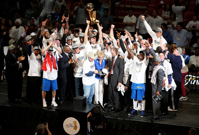 MIAMI, FL - JUNE 12:  Dirk Nowitzki #41 of the Dallas Mavericks holds up the Larry O'Brien trophy as he celebrates with his teamates and team owner Mark Cuban aftre the Mavericks won 105-95 against the Miami Heat in Game Six of the 2011 NBA Finals at Amer