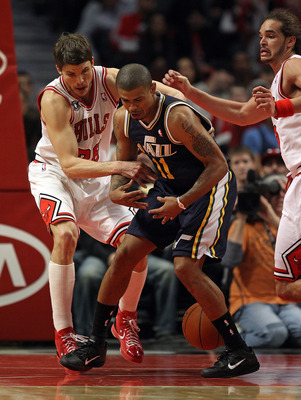 CHICAGO, IL - MARCH 12: Kyle Korver #26 of the Chicago Bulls knocks the ball away from Earl Watson #11 of the Utah Jazz as Joakim Noah #13 defends at the United Center on March 12, 2011 in Chicago, Illinois. The Bulls defeated the Jazz 118-100. NOTE TO US