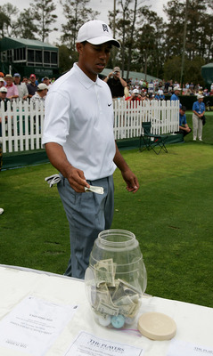 PONTE VEDRA BEACH, FL - MARCH 23:  Tiger Woods thows a one hundred dollar bill into the charity pot on the 17th tee during practice prior to The Players Championship at the TPC at Sawgrass on March 23, 2005 in Ponte Vedra Beach, Florida.  (Photo by Richar