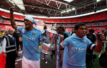 LONDON, ENGLAND - MAY 14:  Vincent Kompany (L) and Carlos Tevez of Manchester City celebrate with the trophy following the FA Cup sponsored by E.ON Final match between Manchester City and Stoke City at Wembley Stadium on May 14, 2011 in London, England.
