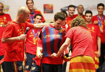 MADRID, SPAIN - JULY 12:  Pepe Reina (L) Gerard Pique (hidden) and Carles Puyol of the Spanish national football team put a FC Barcelona shirt on team mate Cesc Fabregas during the Spanish team's victory parade following their victory over the Netherlands