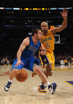 LOS ANGELES, CA - MARCH 31:  Jose Barea #11 of the Dallas Mavericks dribbles past Derek Fisher #2 of the Los Angeles Lakers at Staples Center on March 31, 2011 in Los Angeles, California.  NOTE TO USER: User expressly acknowledges and agrees that, by down