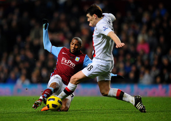 BIRMINGHAM, ENGLAND - JANUARY 22:  Ashley Young of Aston Villa and former teammate Gareth Barry of Manchester City compete for the ball during the Barclays Premier League match between Aston Villa and Manchester City at Villa Park on January 22, 2011 in B