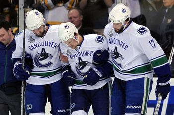 BOSTON, MA - JUNE 13:  Christopher Higgins #20 and Ryan Kesler #17 help Mason Raymond #21 of the Vancouver Canucks off the ice after being checked by Johnny Boychuk #55 of the Boston Bruins in the first period during Game Six of the 2011 NHL Stanley Cup F