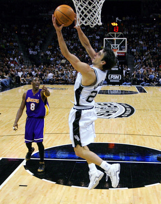 SAN ANTONIO - NOVEMBER 29:  Guard Manu Ginobili #20 of the San Antonio Spurs makes a reverse basket against Kobe Bryant #8 of the Los Angeles Lakers on November 29, 2005 at the SBC Center in San Antonio, Texas.  NOTE TO USER: User expressly acknowledges a