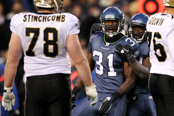 SEATTLE, WA - JANUARY 08:  Kam Chancellor #31 of the Seattle Seahawks reacts as Jonathan Stinchcomb #78 of the New Orleans Saints looks on during the 2011 NFC wild-card playoff game at Qwest Field on January 8, 2011 in Seattle, Washington.  (Photo by Otto