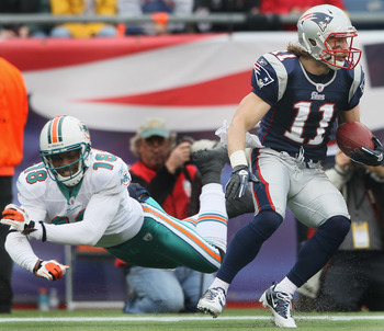 FOXBORO, MA - JANUARY 02:  Julian Edleman #11 of the New England Patriots avoids Roberto Wallace #18 of the Miami Dolphins on January 2, 2011 at Gillette Stadium in Foxboro, Massachusetts.  (Photo by Elsa/Getty Images)