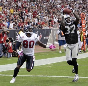 HOUSTON - OCTOBER 04:  Cornerback Chris Johnson #37 of the Oakland Raiders intercepts a pass intended for wide receiver Andre Johnson #80 of the Houston Texans in the first half at Reliant Stadium on October 4, 2009 in Houston, Texas.  (Photo by Bob Levey