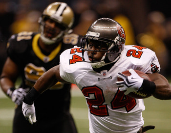 NEW ORLEANS - DECEMBER 27:  Cadillac Williams #24 of the Tampa Bay Buccaneers runs past Will Smith #91 of the New Orleans Saints at the Louisiana Superdome on December 27, 2009 in New Orleans, Louisiana.  (Photo by Chris Graythen/Getty Images)
