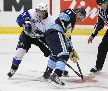MISSISSAUGA, CANADA - MAY 20:  Jonathan Huberdeau #11 of the Saint John Sea Dogs battles with Casey Cizikas #11 of the Mississauga St. Michael's Majors in the opening game of the 2011 Mastercard Memorial Cup in Mississauga, Canada. (Photo by Claus Anderse