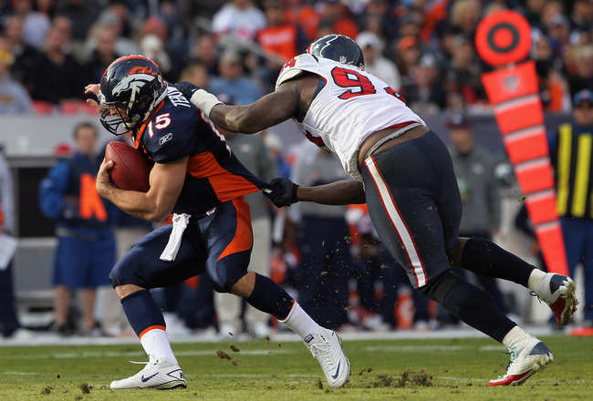DENVER - DECEMBER 26:  Quarterback Tim Tebow #15 of the Denver Broncos eludes a sack attempt by defensive end Antonio Smith #94 of the Houston Texas at INVESCO Field at Mile High on December 26, 2010 in Denver, Colorado.  (Photo by Doug Pensinger/Getty Im