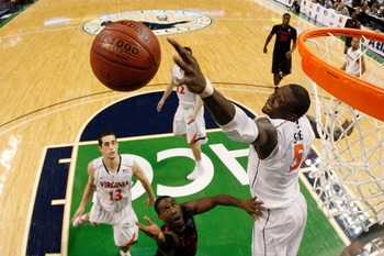 GREENSBORO, NC - MARCH 10:  Assane Sene #5 of the Virginia Cavaliers blocks a shot by during the first round of the 2011 ACC men's basketball tournament at the Greensboro Coliseum on March 10, 2011 in Greensboro, North Carolina.  (Photo by Streeter Lecka/