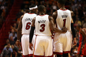MIAMI - NOVEMBER 06:  Dwyane Wade #3, LeBron James #6 and Chris Bosh #1 of the Miami Heat chat during a game against the New Jersey Nets  at American Airlines Arena on November 6, 2010 in Miami, Florida. NOTE TO USER: User expressly acknowledges and agree