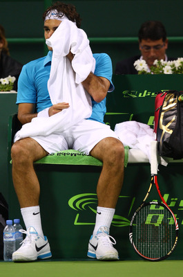 DOHA, QATAR - JANUARY 08:  A dejected looking Roger Federer of Switzerland takes a break during his match against Nikolay Davydenko of Russiain during the Semi- final match of the ATP Qatar ExxonMobil Open at the Khalifa International Tennis and Squash Co