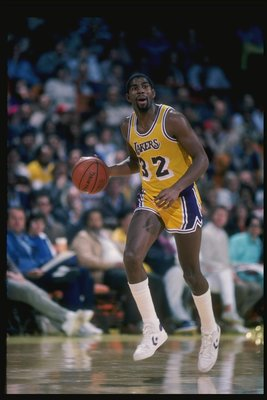 Guard Magic Johnson of the Los Angeles Lakers driibbles the ball down the court during a game at the Great Western Forum in Inglewood, California.