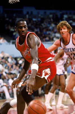 LOS ANGELES, CA - DECEMBER 1984:  Michael Jordan #23 of the Chicago Bulls moves the ball against Bill Walton #32 of the Los Angeles Clippers during a December 1984 season game at the Sports Arena in Los Angeles, California.  (Photo by Rick Stewart/Getty I