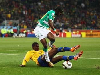 JOHANNESBURG, SOUTH AFRICA - JUNE 20: Juan of Brazil tackles Gervinho of Ivory Coast during the 2010 FIFA World Cup South Africa Group G match between Brazil and Ivory Coast at Soccer City Stadium on June 20, 2010 in Johannesburg, South Africa.  (Photo by