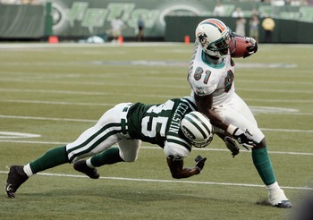 EAST RUTHERFORD, NJ - SEPTEMBER 18:  Tight end Randy McMicheal #81 of the Miami Dolphins tries to avoid safey Oliver Celestin #45 of the New York Jets during their game on September 18, 2005 at Giants Stadium in East Rutherford, New Jersey. The Jets defea