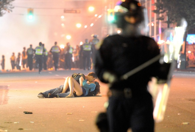 VANCOUVER, BC - JUNE 15:  Riot police walk in the street as a couple kiss on June 15, 2011 in Vancouver, Canada. Vancouver broke out in riots after their hockey team the Vancouver Canucks lost in Game Seven of the Stanley Cup Finals.  (Photo by Rich Lam/G